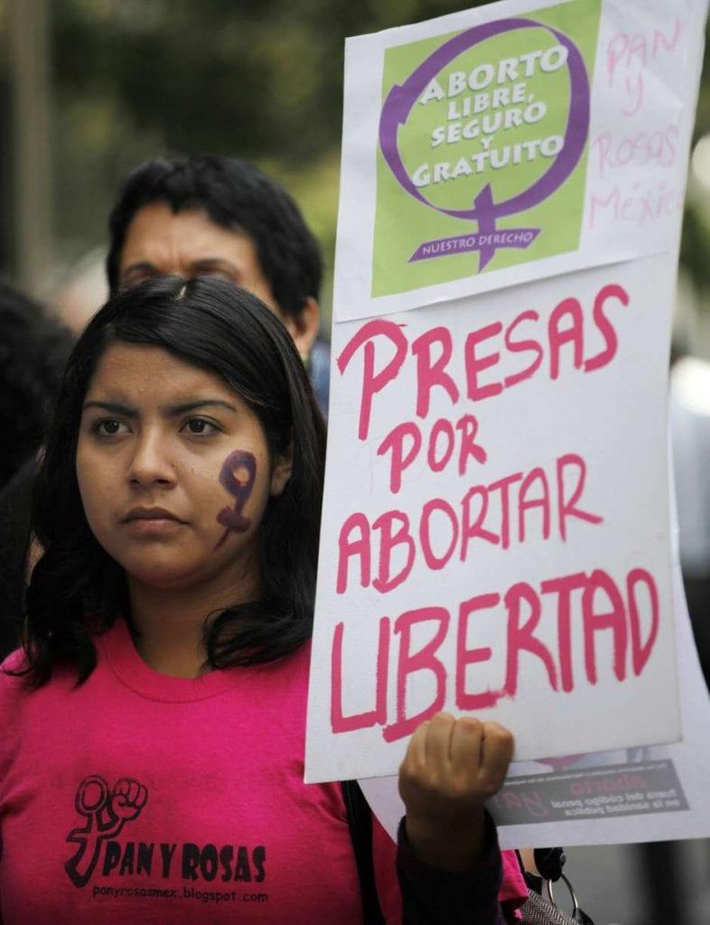 Mujer con pancarta contra penas por abortar