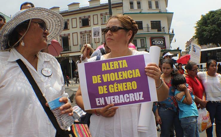 Mujer con cartel con leyenda alerta de violencia de género en Veracruz