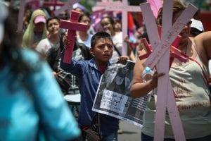 Personas marchan con cruces rosas en el día de la no violencia contra las mujeres