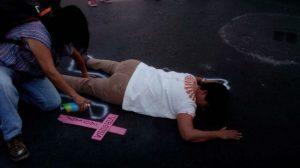 Mujeres dibujan siluetas simulando escena de un feminicidio