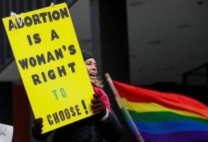 Mujer con pancarta por reformas de Trump en contra del aborto
