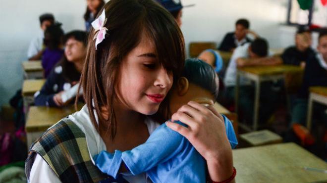 Adolescente en edad escolar en una aula de clases sosteniendo un bebé.