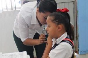 Niña en edad escolar recibiendo vacuna contra el VPH por parte de una enfermera