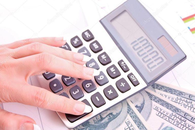 Mujer hace cuentas en una calculadora