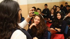 Maestra muestra píldora anticonceptiva a grupo de jóvenes