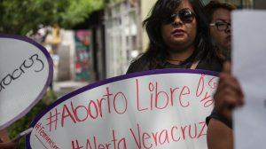 """Mujer en una marcha sosteniendo una pancarta que se lee """"Aborto libre, Alerta Veracruz""""."""