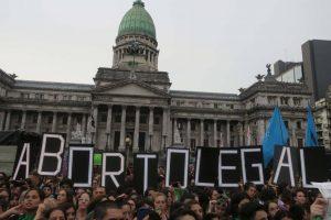 Imagen de manifestación solicitando con una pancarta el aborto legal.