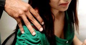 Perfil de una adolescente con cara incómoda mientras es tocada por una mano en el hombro.