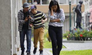 Par de jóvenes miran su celular riéndose mientras adelante de ellos camina una joven con gesto afligido.