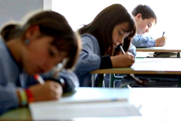 Niñas en colegio escriben sobre sus libretas