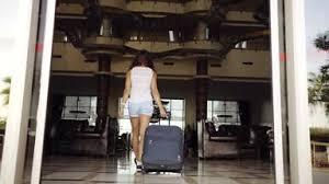 Mujer joven entra en hotel con maleta