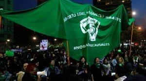 """Manifestación en Chile en donde se ve un pañuelo verde gigante con las consignas """"Aborto libre, seguro y gratuito"""" y """"No bastan tres causales""""."""