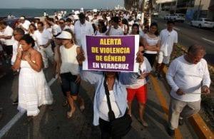 """Personas marchando en el puerto de Veracruz vestidos de blanco. Una mujer sujeta una pancarta que dice """"Alerta de violencia de género en Veracruz""""."""