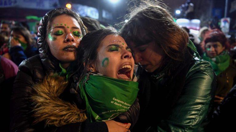 Tres mujeres vestidas con motivos verdes cierran los ojos abrazadas mientras la de en medio lanza un grito en desaprobación al rechazo de la Ley IVE.